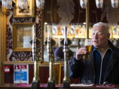 A customer enjoys a drink at the bar (Jane Barlow/PA)