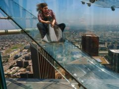 A member of the media rides down a glass slide during a media preview at the US Bank Tower building in Los Angeles (Richard Vogel/AP)