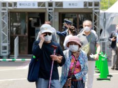 Elderly people go out of the newly opened mass vaccination centre after receiving the Moderna coronavirus vaccine in Tokyo (Koji Sasahara/AP)