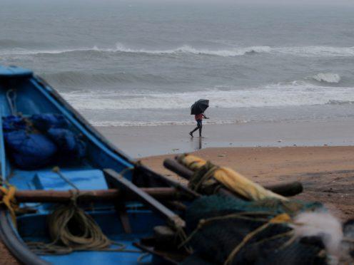 A man walks holding an umbrella on a beach on the Bay of Bengal coast in Odisha, India (AP Photo)