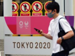A man walks past a banner for the Tokyo 2020 Olympic and Paralympic Games in Tokyo (Eugene Hoshiko/AP)