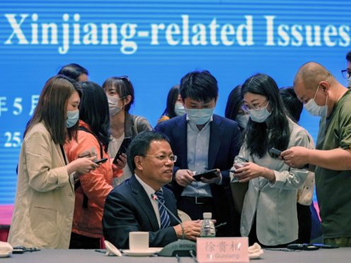 Xu Guixiang, a spokesperson for the Xinjiang north-western region's government, is surrounded by reporters. China has denounced a people's tribunal planned for the UK over allegations of genocide being committed against Uyghurs and other Turkic Muslim people in the Xinjiang region (Andy Wong/AP)