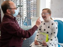 Dispensing Optician Ian Rampton from the University of Portsmouth helps Rosie Johnson, 14, try on her new glasses (Andrew Matthews/PA)