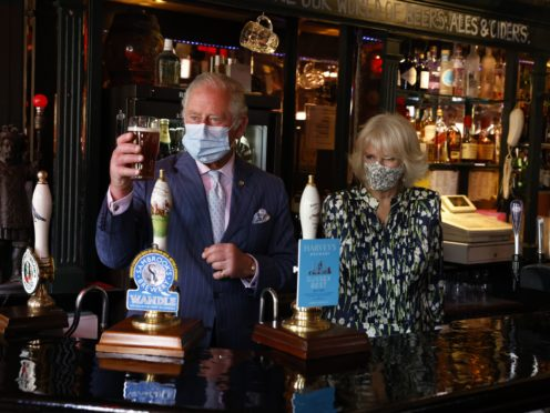 Camilla watches as Charles studies a pint he pulled in the Prince of Wales pub in Clapham, south London (Heathcliff O'Malley/Daily Telegraph/PA)
