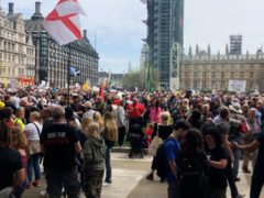 People take part in an anti-vaccine protest in Parliament Square (Tess De La Mare/PA)