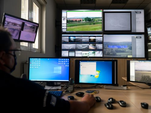 A police officer works inside the operation centre at the village of Nea Vyssa, near the Greek-Turkish border, in Greece (Giannis Papanikos/AP)