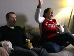 Kirsty and Alastair Jennings celebrate Arsenal's winner against Brighton on December 28 on their sofa, one of the fan images that will form part of a new Homes Of Football exhibition at the National Football Museum (Handout from Stuart Roy Clarke and Amazon Prime Video/PA)