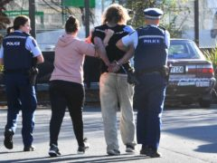 Police take a suspect into custody near the Countdown supermarket in Dunedin, New Zealand (Otago Daily Times via AP)