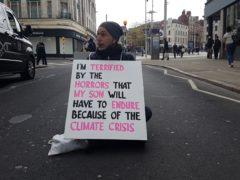 A climate protester blocks Wheeler Gate in Nottingham city centre(Diana Schmies/PA)