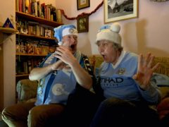 Lifelong Manchester City fans Cath and Dougal Brice react as Raheem Sterling puts them in front against Southampton in a match shown live by Amazon on December 19, 2020. The picture is part of a new Homes Of Football exhibition at the National Football Museum in Manchester (Handout from Stuart Roy Clarke and Amazon Prime Video/PA)