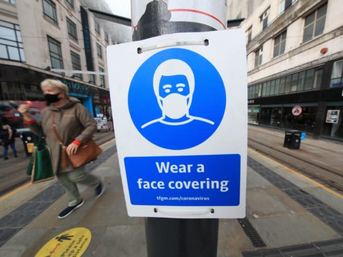 A sign advising on wearing face coverings at a tram stop in Manchester (PA)