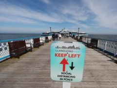 A social distancing sign on the pier in Llandudno, Wales, where lockdown restrictions have eased (Peter Byrne/PA)