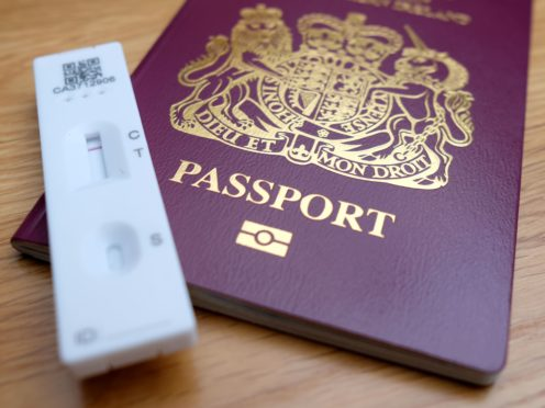 A negative Covid-19 test sits on top of a Passport for the United Kingdom of Great Britain and Northern Ireland. (Andrew Matthews/PA)