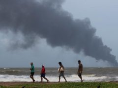 Impoverished Sri Lankans walk along the beach as they try to salvage wreckage washed off to the shore from the burning Singaporean ship MV X-Press Pearl (Eranga Jayawardena/AP)