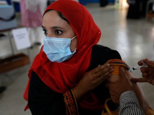 A teacher receives the first jab of the Sinovac coronavirus vaccine from a paramedic in a vaccination centre at a school, in Lahore, Pakistan (K.M. Chaudary/AP)
