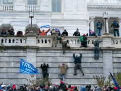 Violent insurrectionists loyal to President Donald Trump scale the west wall of the the US Capitol in Washington (Jose Luis Magana/AP)