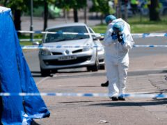 A forensics officer at the scene on College Road, Kingstanding (Jacob King/PA)