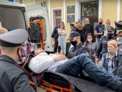 Police officers and paramedics carry Stsiapan Latypau, a Belarusian activist who stabbed himself with a pen during a court hearing to protest political repression, into an ambulance in Minsk, Belarus. (Radio Free Europe/Radio Liberty via AP)