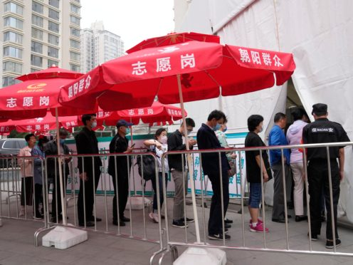 Residents line up outside a vaccination centre in Beijing (Ng Han Guan/AP)