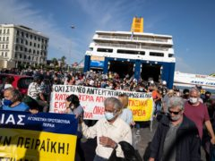 Protesters hold placards as they leave from the port of Piraeus port, near Athens, on Thursday, June 3, 2021. Ferry services to the Greek islands were disrupted Thursday morning after a seamen's union went ahead with a strike that a court had declared illegal.(AP Photo/Petros Giannakouris)