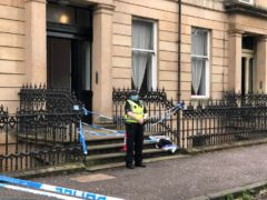 A police officer stands guard outside the tenement where Esther Brown's body was found (Douglas Barrie/PA)