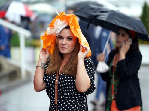 A Racegoer shelters from the rain during day one of the Cazoo Derby Festival at Epsom Racecourse (Mike Egerton/Jockey Club/PA)