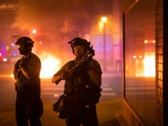 Police stand guard after protesters start fires after a vigil was held for Winston Boogie Smith Jr (AP)