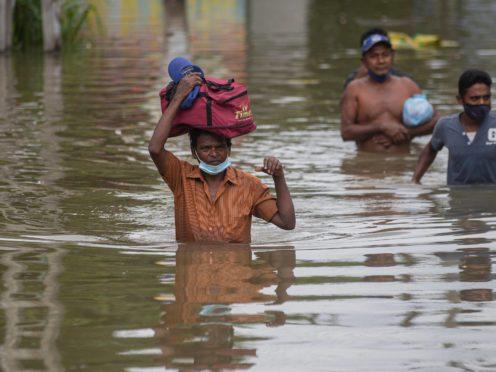 Sri Lankans wade through an inundated street (AP)