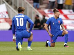 Jack Grealish and Kalvin Phillips take a knee before England's game with Romania (Lee Smith/PA)