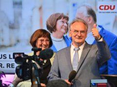 Saxony-Anhalt state governor Reiner Haseloff of Angela Merkel's Christian Democratic Union party, CDU, and his wife Gabriele react, at the CDU election party (Bernd Von Jutrcznka/AP)