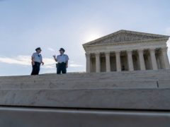 Police officers talk in front of the Supreme Court in Washington (Andrew Harnik/AP)