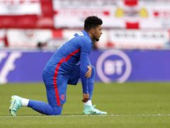 England forward Jadon Sancho takes the knee before last Sunday's match against Romania (Lee Smith/PA)