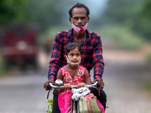 An Indian villager and a child wearing masks ride on a bicycle on the outskirts of Gauhati, India (Anupam Nath/AP)