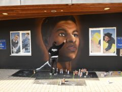 Josh from street artists MurWalls paints a mural of footballer Marcus Rashford on the wall of Gainsborough Primary School (Stefan Rousseau/PA)