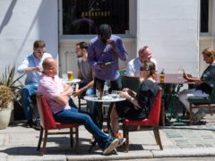 People eat and drink at tables outside a pub (Dominic lipinski/PA)