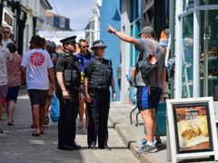 Police officers speak to a member of the public in St Ives (Ben Birchall/PA)