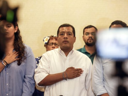Felix Maradiaga, centre, stands at attention as the national anthem is sung (Alfredo Zuniga/AP)