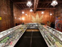 A worker cleans a display case at the Ganja Goddess Cannabis Store in Seattle. Washington states 'joints for jabs' programme is off to a rocky start (Ted S Warren/AP)