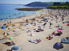 People enjoy the sunshine on Gyllyngvase Beach near Falmouth in Cornwall (Aaron Chown/PA)