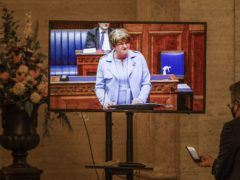 Arlene Foster appears on a television screen giving her resignation speech (Liam McBurney/PA)