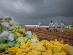 Sri Lankan sailors tidy up debris from the stricken ship on a beach near Colombo (Eranga Jayawardena/AP)