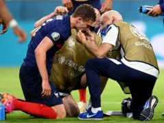 Benjamin Pavard receives treatment after his collision with Germany's Robin Gosens on Tuesday night (Matthias Hangst/AP)