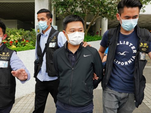 Ryan Law, Apple Daily's chief editor, is arrested by police officers in Hong Kong on Thursday (AP)
