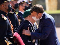 Emmanuel Macron gives the traditional cheek embrace to Second World War veteran Leon Gautier (Michel Euler/AP)