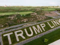 Patrons play golf near a giant branding sign at Trump Golf Links at Ferry Point in the Bronx. The Trump Organisation is suing New York City over the course (John Minchillo/AP)