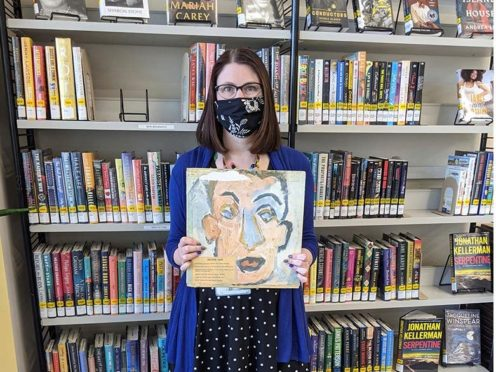 Sara Phillips, a branch manager at Heights Libraries in Ohio, holds the Bob Dylan album (Heights Libraries via AP)