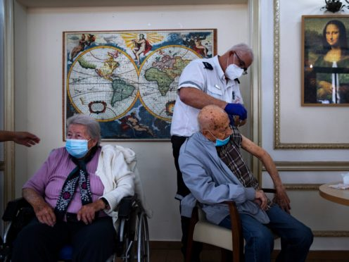 A man receives his second Pfizer-BioNTech Covid-19 vaccine from a Magen David Adom national emergency service volunteer at a private nursing home, in Ramat Gan, Israel (Oded Balilty/AP)