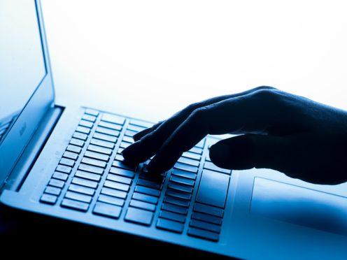 A woman's hand presses a key of a laptop keyboard.