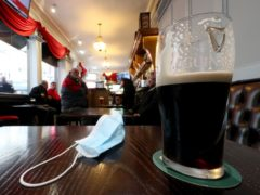 A close up of a pint of Guinness and a face mask (PA)