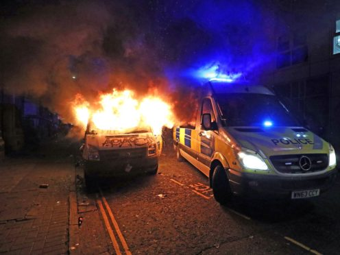 A vandalised police van on fire outside Bridewell Police Station (Andrew Matthews/PA)
